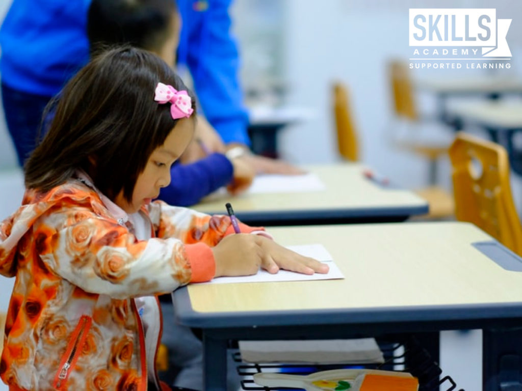 A young child reading through her notes at her classroom desk. Be a part of a child's learning experience with our Educare Courses.