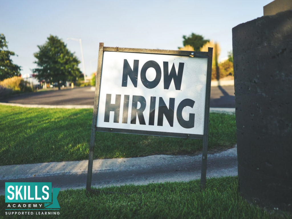 A 'Now Hiring' sign displayed on a field. Learn how the hiring process works and more by enrolling in our Human Resource Management Courses.