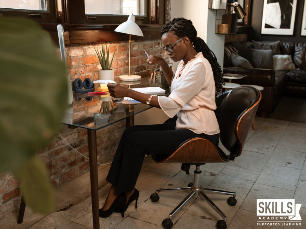 Lady sitting at a desk doing admin work. Learn how to enhance your skills with Office Administration Courses with us