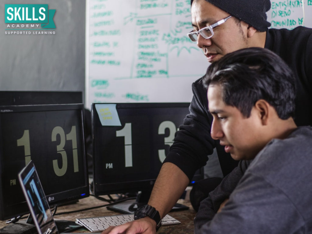 Two men working with computers. Get these skills with our computer courses.