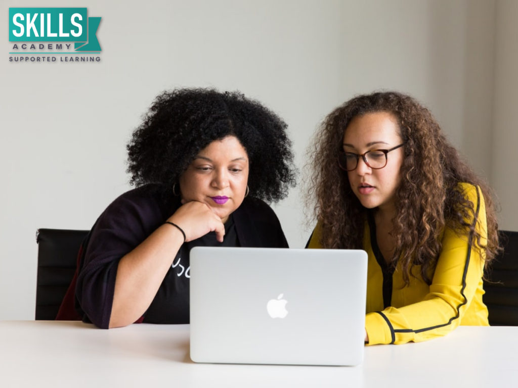 Two women researching courses that only require grade 11 on their computer.