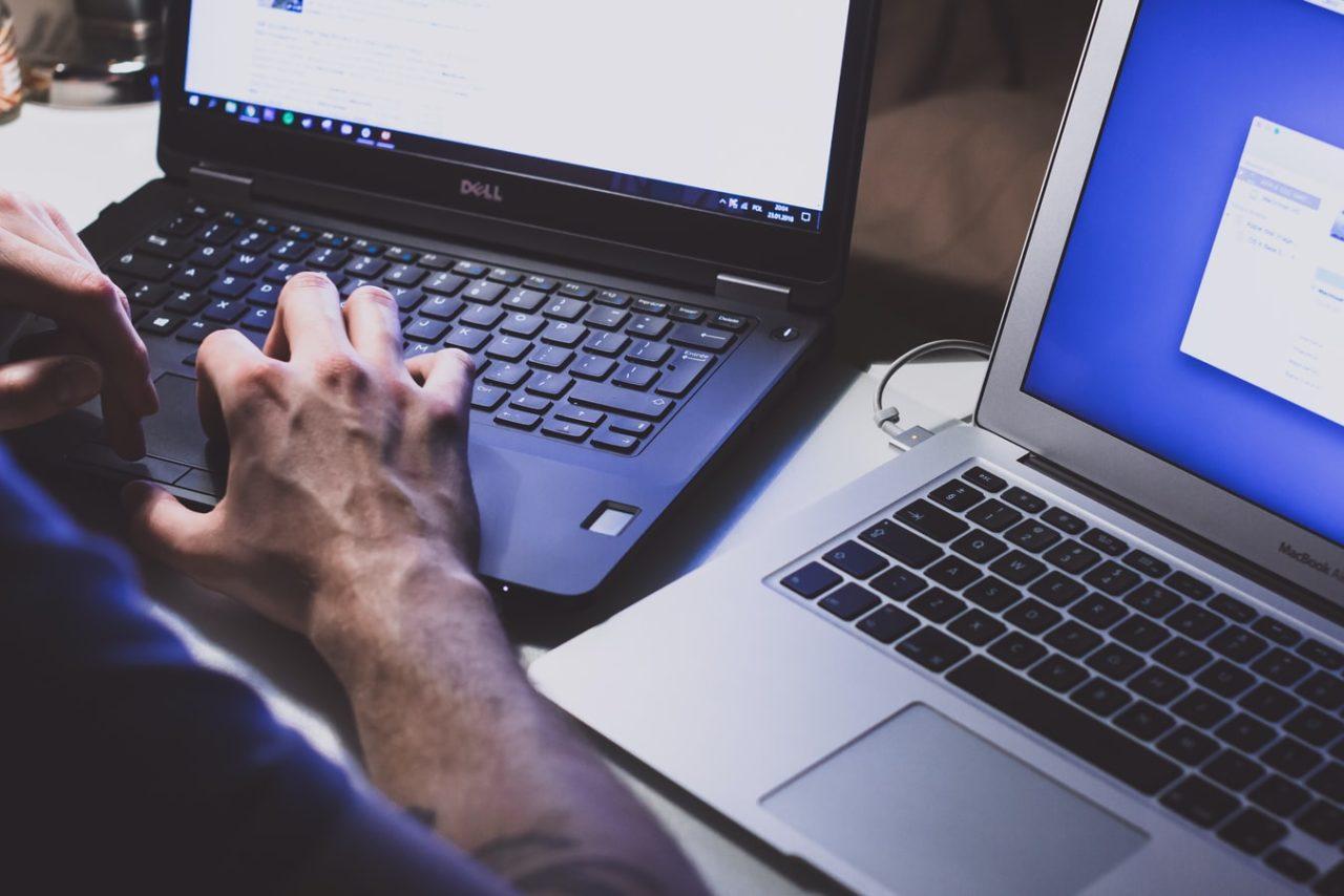 IT technician working on two laptops