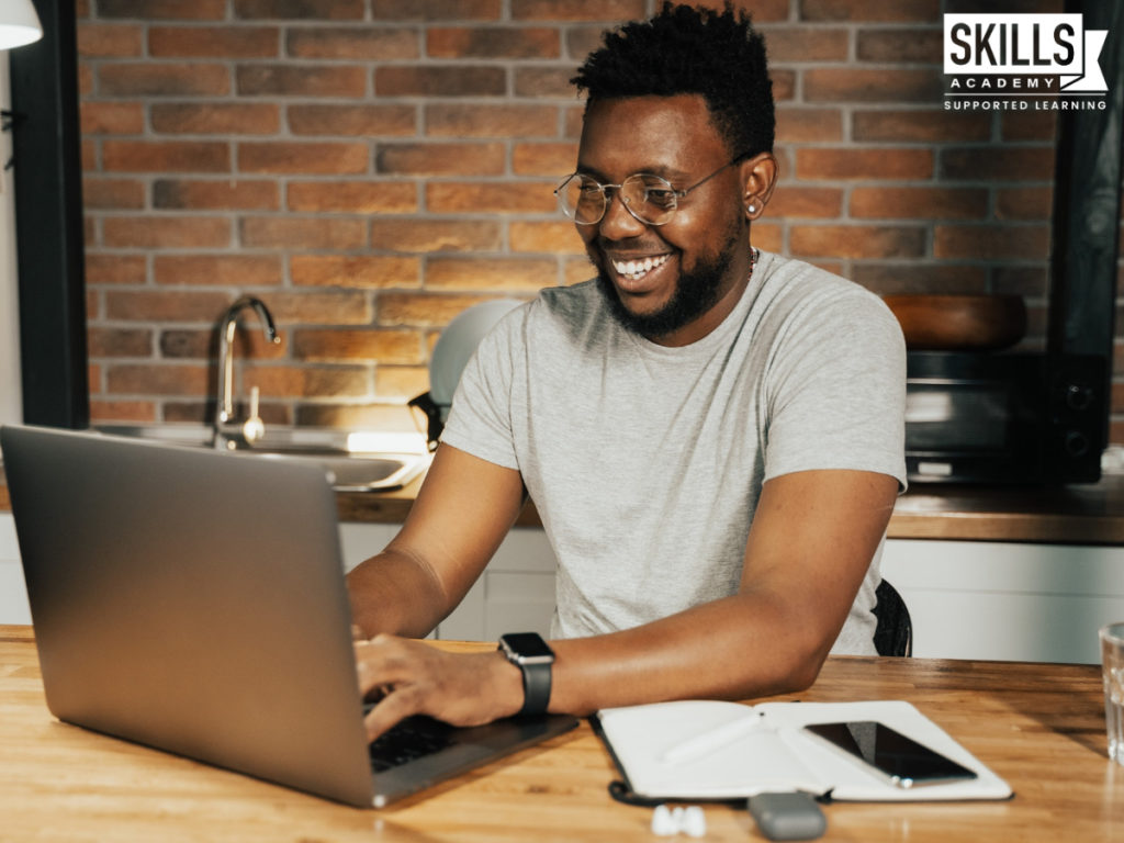 Man wearing a grey sweater sitting in front of a laptop smiling. Workplace Skills Will help you complete your work and stay-on-track.