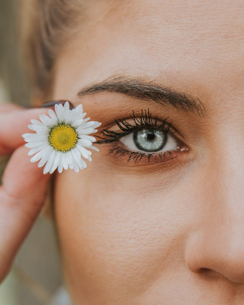 A woman's side face adorned with beauty products. She has grey blue eyes and is carrying a flower next to her eye