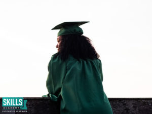 Student wearing graduation regalia after studying acredited courses