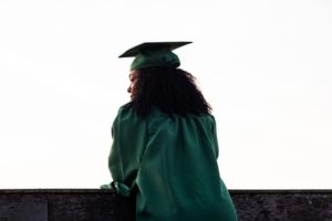 A student in green graduation regalia leaning over a retaining wall