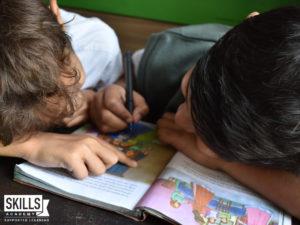 Children in childcare writing in a book