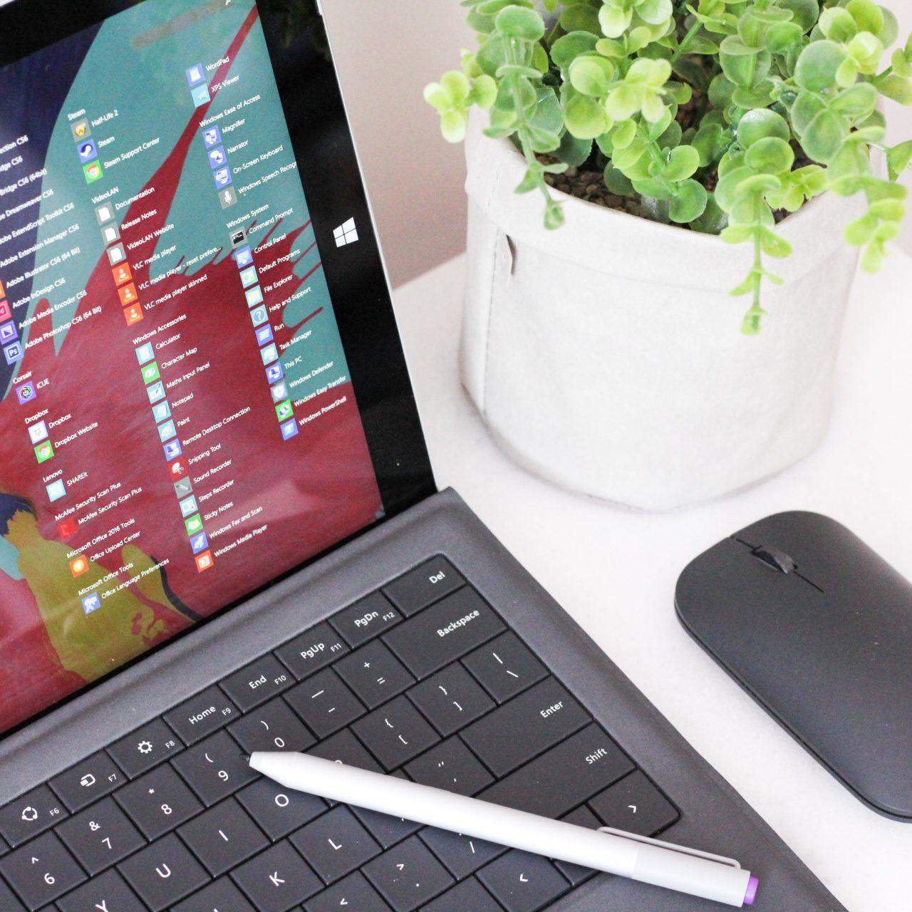 Microsoft laptop and a mouse next to a pot plants
