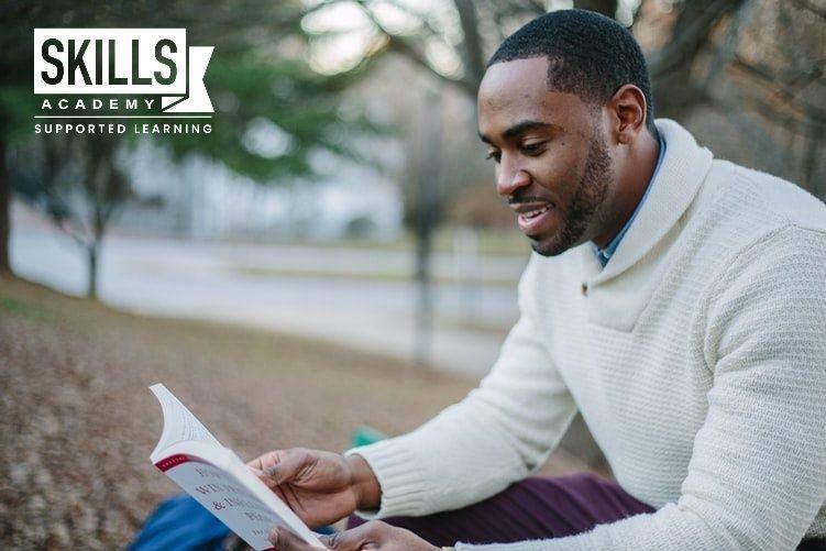 A young man reading through his course textbook