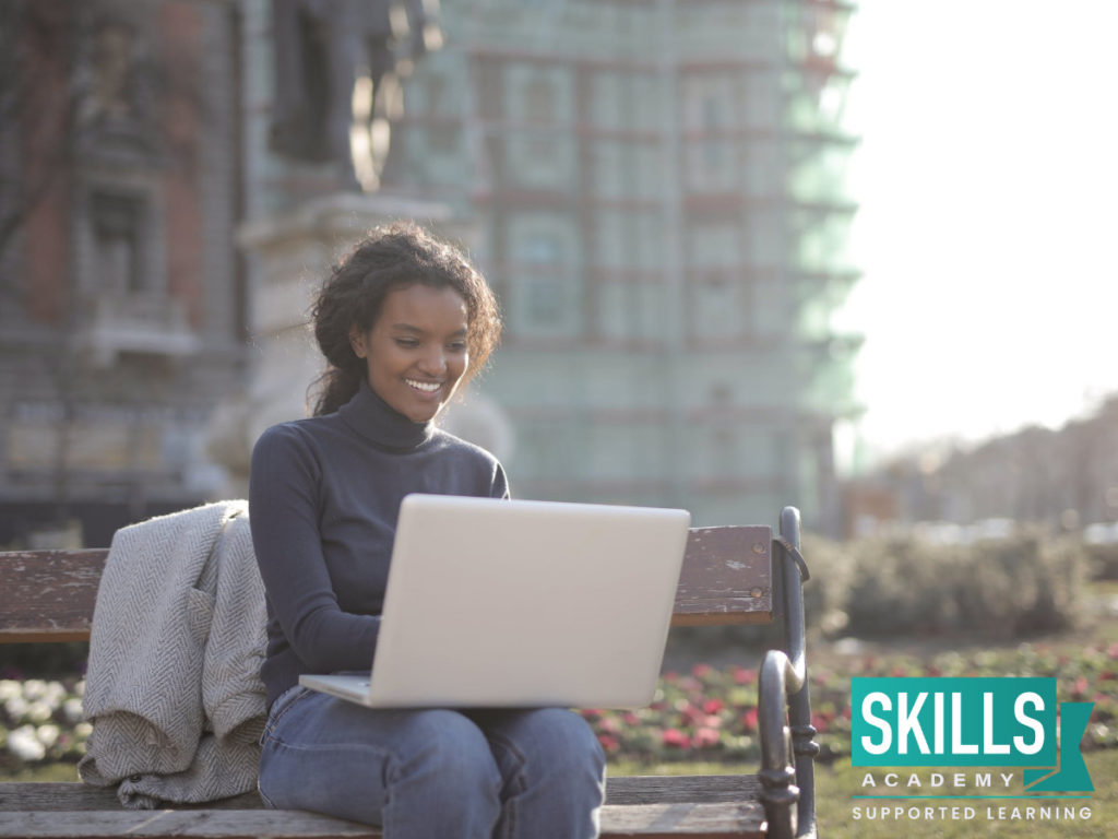 A young girl sitting on a park bench with her laptop smiling because she found Tips on How to Network.