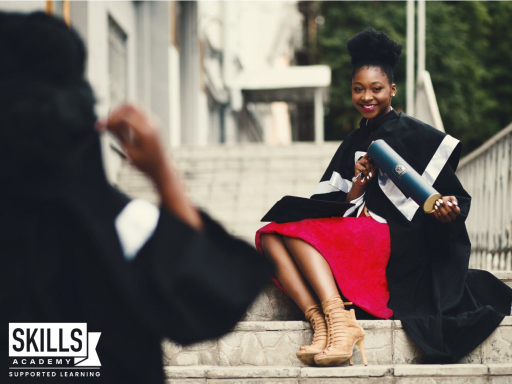A student who found out how to get a bursary, wearing a red dress and her graduation cap and gown, sitting on steps with her diploma getting her picture taken.