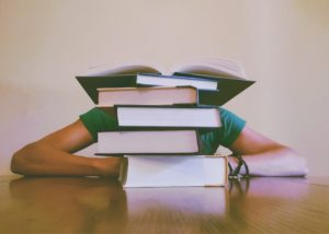 Student with a stack of books. Studying During the Holidays doesn't have to be chore.
