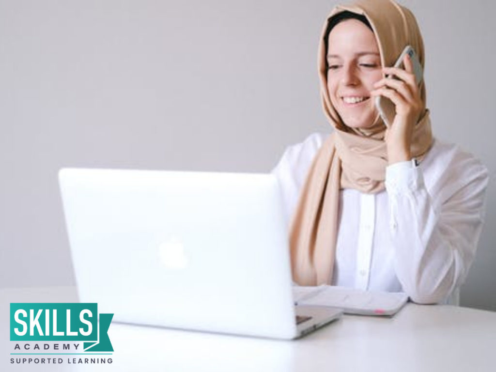 A young girl wearing a hijab. Sitting at her desk, taking her online class while on the phone with her classmate, she studies via Distance Learning: The New Normal.