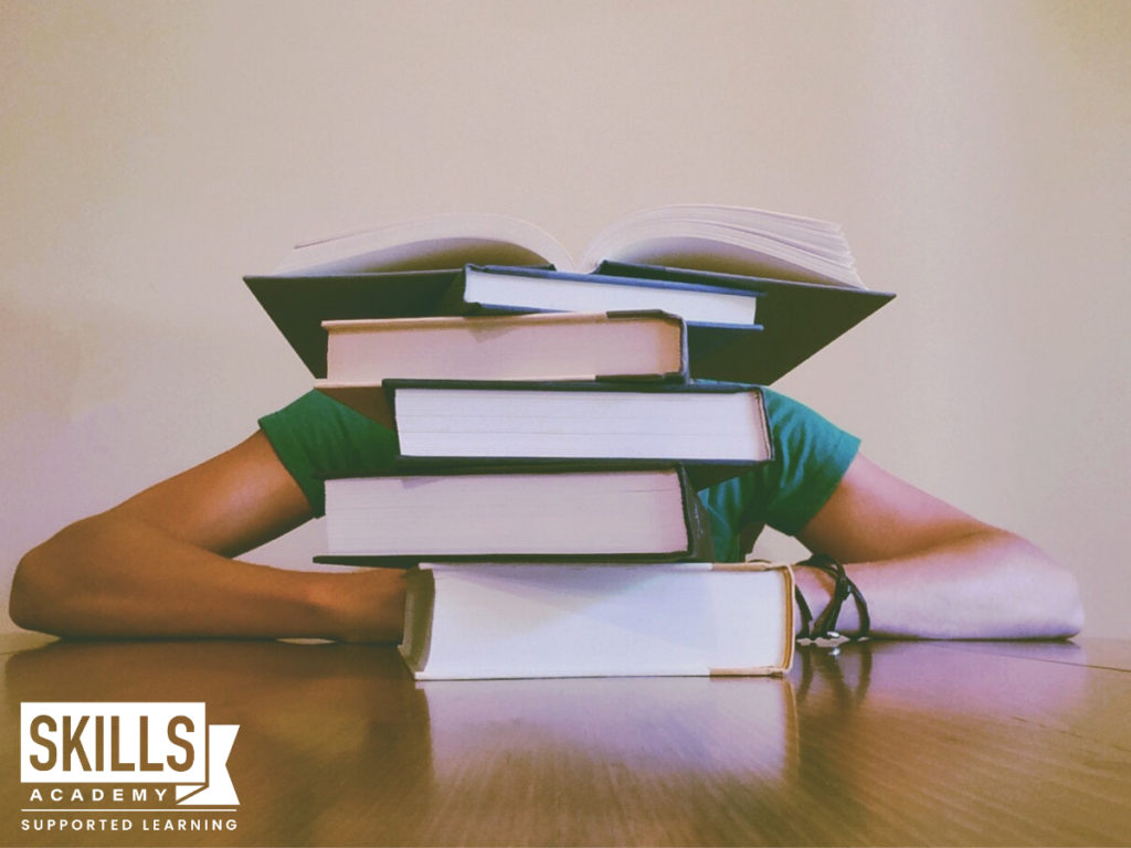 Student with a stack of textbooks in front of him. Cramming before an exam is one of the biggest mistakes you can make. Learn What to Avoid When Studying right here.