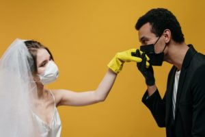 Man and woman wearing face masks and gloves to get married during covid. This is How Covid-19 Changed the Events Industry