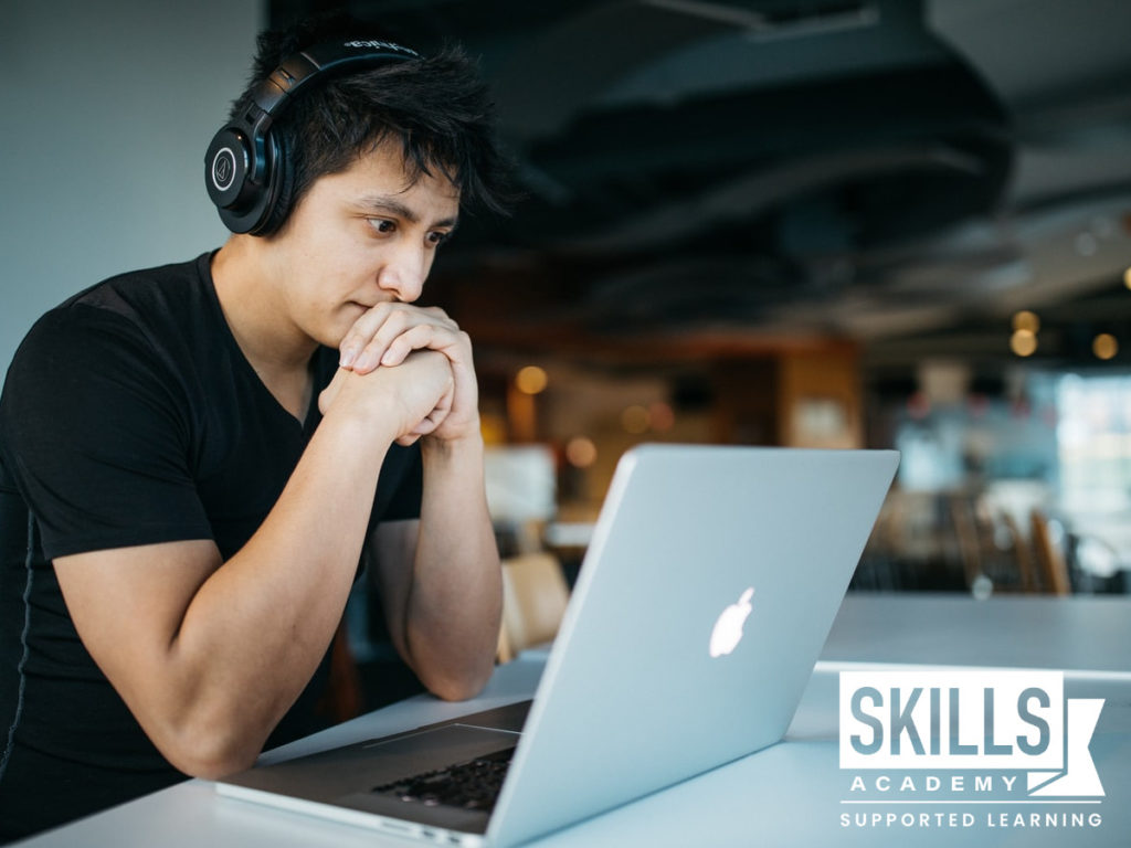A young man with headphones on, sitting in front of his computer reading up on Leaked Matric Exam Papers.