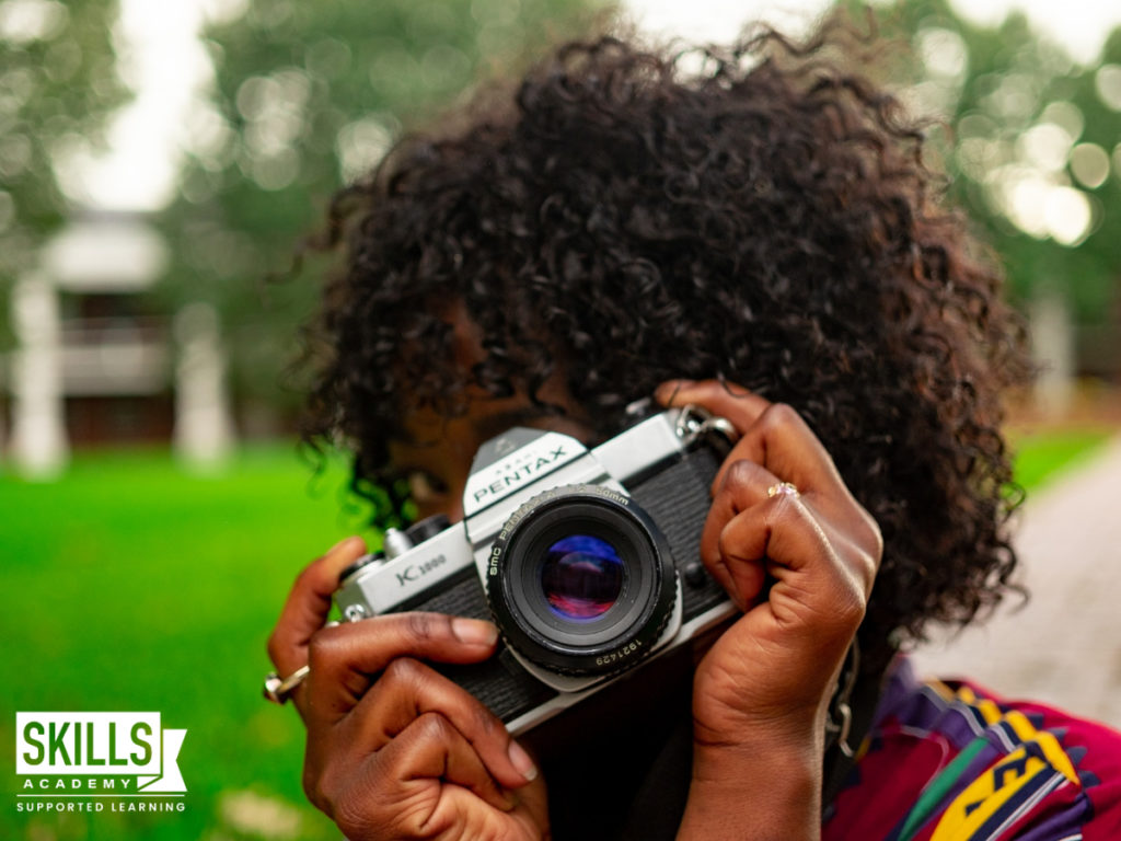 Woman holding a camera to her face, taking a photo outside. Learn what are your chances of getting a job with course specific careers right here.