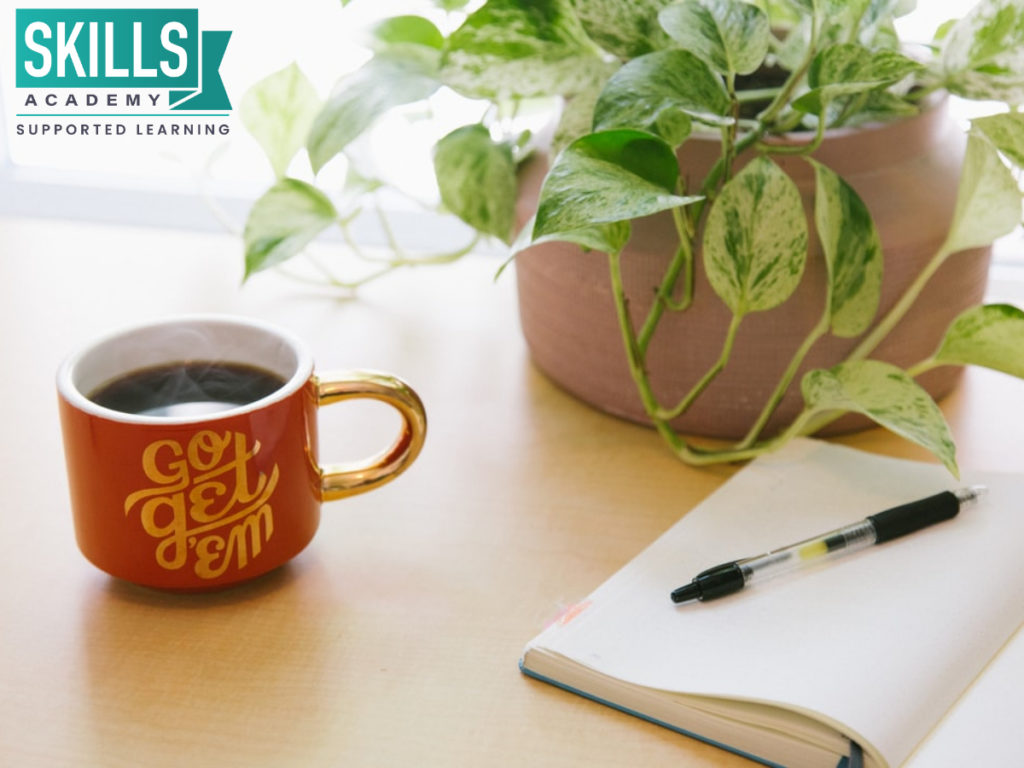 A coffee cup placed next to a notebook. Here's how to continue your studies when you have other responsibilities