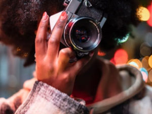 Woman holding up a camera and taking a photo. Here are the benefits of studying photography